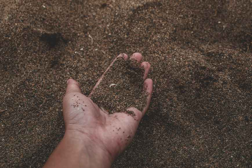 close up photo of person holding sand
